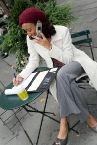 Sterke onafhankelijke vrouw werkt buiten aan een tafeltje met telefoon en notitieblok